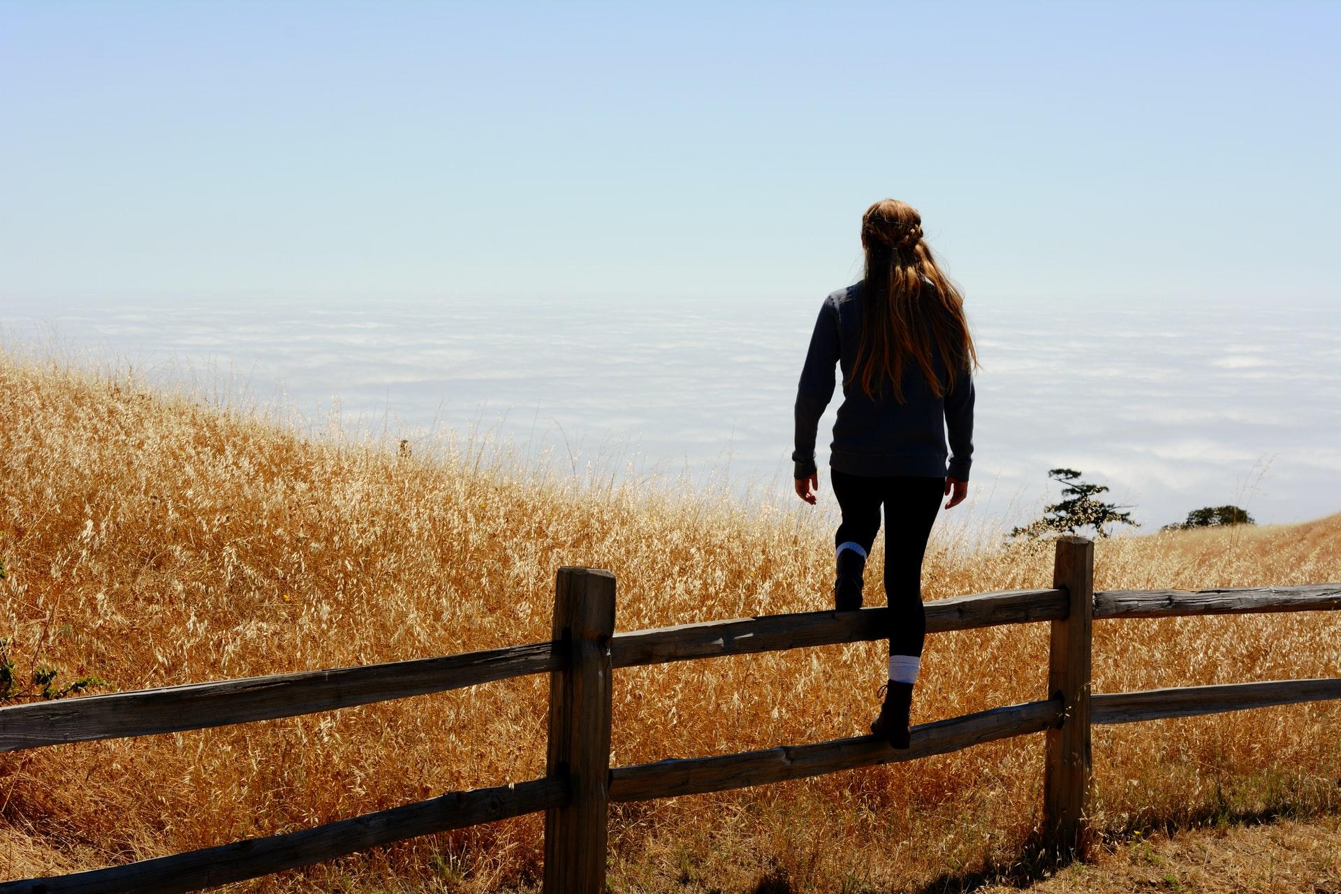 kvinna klättrar över ett staket